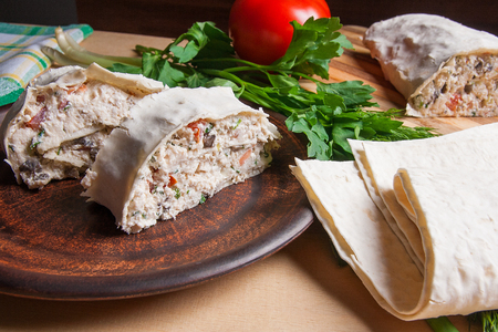 Pieces of thin Armenian pita bread or lavash wrapped tomatoes, cottage cheese or curd, chicken meat, tomatoes and herbs - dill, onion, parsley and brown clay plate. Red ripe tomato, lavash to pita, herbs and cutting board on background. Composition in rus Stok Fotoğraf - 81291239