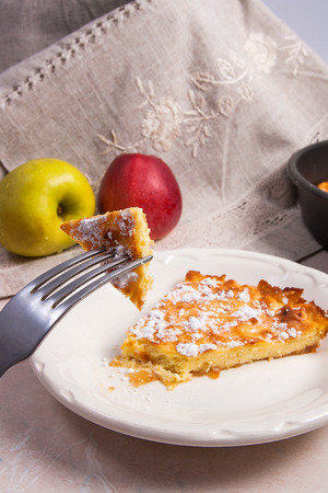 white backing: Slice of homemade apple pie on white plate and fork . Homemade freshly baked apple pie in backing form with apples. Several organic red and green apples in the background.