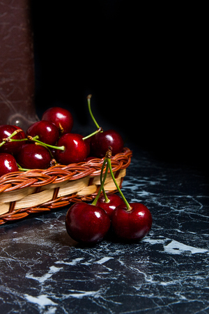 concep: Close up view of several red sweet cherries on the marble table and ripe sweet cherries in yellow wooden basket on background. Composition in rustic style - organic red sweet cherries in vintage wooden basket on dark marble background. Healthy food concep Stock Photo