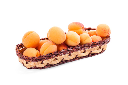 Group of harvested ripe apricots in yellow wooden basket isolated on white background. Healthy food concept. Harvest time.