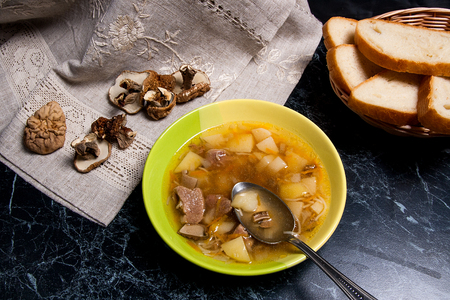 Mushroom soup in green plate with metal spoon on a black stone background. Several dried porcini or white  wild mushrooms on brown cloth. Slices of white bread in basket.