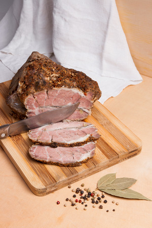 Spicy meat baked with herbs and spice on wooden cutting board. Country style sliced oven-baked spicy ham. A juicy fresh baked pork and pepper with bay leaves on on wooden board.