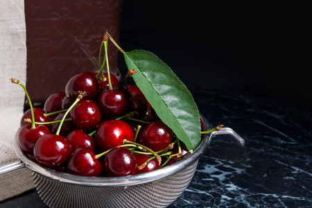Ripe sweet cherries with big green leaf of cherry tree  in steel colander. Composition in rustic style - organic red sweet cherries in steel colander on dark marble background. Healthy food concept. Harvest time. Stock Photo