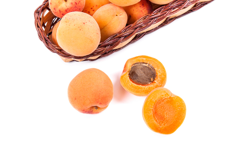 Group of harvested ripe apricots in yellow wooden basket with whole and halved apricots isolated on white background. Healthy food concept. Harvest time. Banque d'images