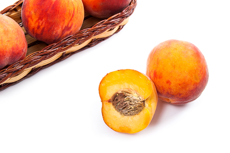 Several whole sweet juicy peach fruit in yellow wooden basket, whole fruits and half of peach in front of the basket isolated on white background