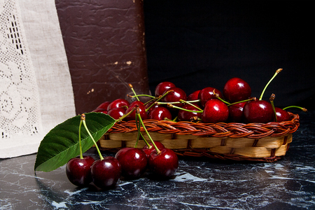 Close up view of several red sweet cherries and big green leaf of cherry tree on the marble table and ripe sweet cherries in yellow wooden basket on background. Composition in rustic style - organic red sweet cherries in vintage wooden basket on dark marble background. Healthy food concept. Harvest time.  Stock Photo