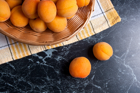 Ripe organic apricots in yellow wooden basket. Composition in rustic style - organic red juicy apricots in vintage wooden basket on dark marble background. Healthy food concept. Harvest time.