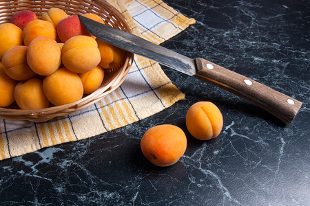 Ripe organic apricots in yellow wooden basket. Composition in rustic style - organic red juicy apricots in vintage wooden basket and vintage knife on dark marble background. Healthy food concept. Harvest time.