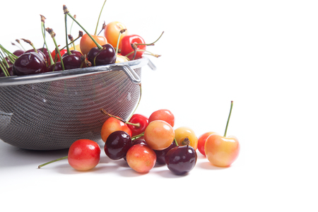Steel colander with ripe berries of yellow and red sweet cherries on white background Archivio Fotografico
