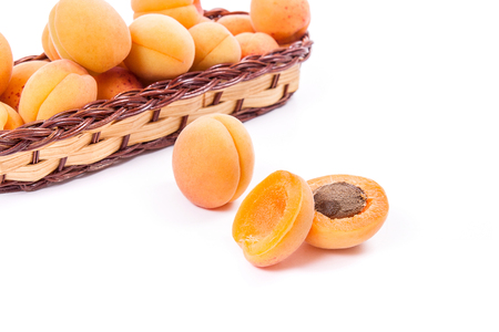 Group of harvested ripe apricots in yellow wooden basket with whole and halved apricots isolated on white background. Healthy food concept. Harvest time.