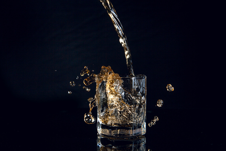 Whiskey pouring into glass with ice isolated on reflective black surface. Whiskey splash out of glass, many drops of beverage get out from glass. Stok Fotoğraf