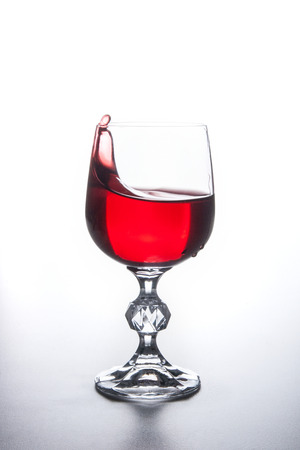 Drinks and beverages conception. Red wine splashing in wine glass with dynamic drops on light background.