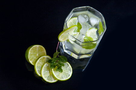 Mojito summer beach refreshing tropical cocktail in glass with soda water, lime juice, mint leaves, sugar, ice and rum on reflective black surface.