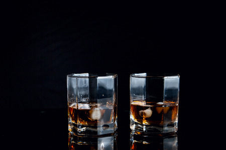 Drinks and beverages conception. Two glasses of whisky with ice cubes on reflective black surface. Stock fotó