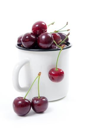 White cup with ripe berries of red sweet cherry and several berries in front of the cup. Composition on a white background.