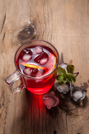 Summer iced drink - hibiscus cold tea with ice and mint. Cup of hibiscus cold tea with ice, lemon and mint on vintage wooden background