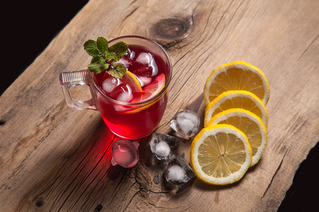 Summer iced drink - hibiscus cold tea with ice, lemon and mint. Cup of hibiscus cold tea with ice, lemon and mint on vintage wooden background. Reklamní fotografie