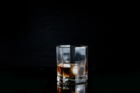 Drinks and beverages conception. Single glass of whisky with ice cubes on reflective black surface.