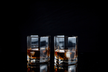Drinks and beverages conception. Two glasses of whisky with ice cubes on reflective black surface. Reklamní fotografie