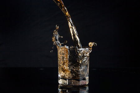 Whiskey pouring into glass with ice isolated on reflective black surface. Whiskey splash out of glass, many drops of beverage get out from glass. Reklamní fotografie