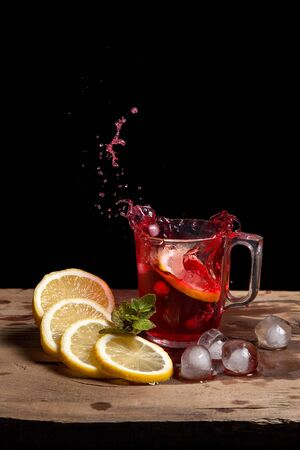 Summer iced drink - hibiscus cold tea with ice, lemon and mint.  Big splash with drops of hibiscus cold tea from the glass of beverage with fallen lemon slice into glass on wooden background. Hibiscus cold tea splash out of glass, many drops of beverage get out from glass.
