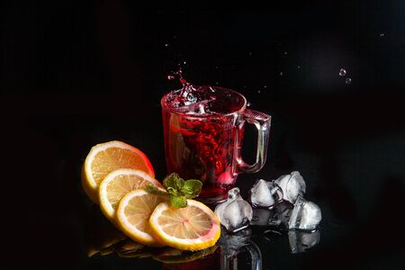 Summer iced drink - hibiscus cold tea with ice, lemon and mint. Big splash with drops of hibiscus cold tea from the glass of beverage with fallen ice cube into glass isolated on reflective black surface. Hibiscus cold tea splash out of glass, many drops of beverage get out from glass. Zdjęcie Seryjne
