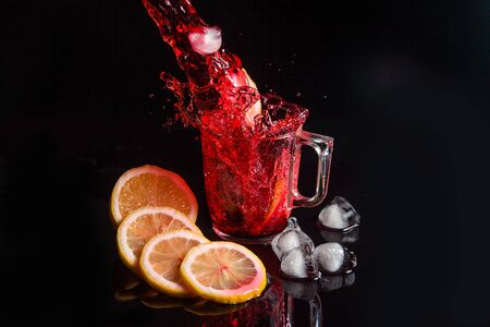 Summer iced drink - hibiscus cold tea with ice, lemon and mint. Hibiscus cold tea pouring into glass with ice isolated on reflective black surface. Hibiscus cold tea splash out of glass, many drops of beverage get out from glass.