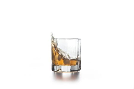 Whiskey splash out of glass, many drops of beverage get out from glass on light background.
