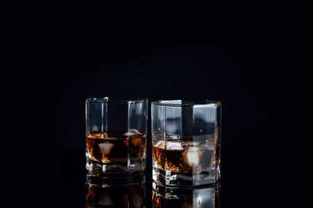 Drinks and beverages conception. Two glasses of whisky with ice cubes on reflective black surface. 写真素材