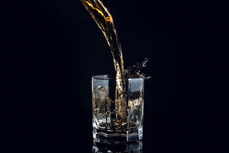 Whiskey pouring into glass with ice isolated on reflective black surface. Whiskey splash out of glass, many drops of beverage get out from glass. 写真素材