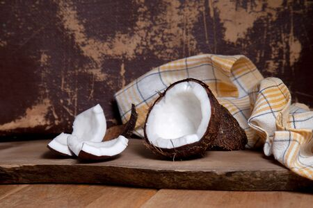 Coconut. Coconut shell, coconut flakes and small pieces of crashed nut on a wooden background. Tropical fruit coconut in the shell. Organic healthy dietary vegan product widely used in cosmetics.