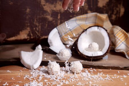 Close up of sweet chocolate coconut truffles and coconut with white pulp, coconut chip. White chocolate coconut sweets and coconut shell, coconut flakes, small pieces of crashed nut, coconut chip on a wooden background.