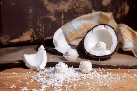 Close up of coconut with white pulp, coconut chip and sweet chocolate coconut truffles. Coconut shell, coconut flakes, small pieces of crashed nut, coconut chip and white chocolate coconut sweets on a wooden background. Reklamní fotografie