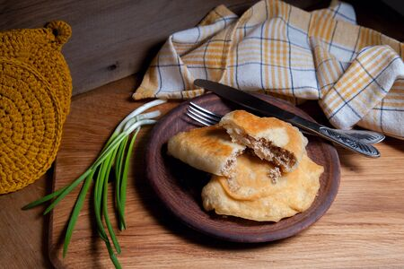 Clay plate with two of individual fried pies with meat on wooden table. Composition of fast food dinner - plate with two pies with pulled pork pastry, cutlery and green onian on vintage wooden background. Stock Photo
