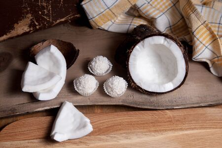 Coconut and sweet chocolate coconut truffles. Coconut shell, coconut flakes, small pieces of crashed nut and white chocolate coconut sweets on a wooden background. Tropical fruit coconut in the shell. Reklamní fotografie