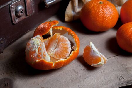 Several of unpeeled whole fresh orange mandarine or oranges, tangerines, clementines, citrus fruits, one fruit is half peeled and slices of peeled mandarin on wooden board