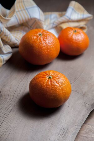 Ripe and juicy mandarins or oranges, tangerines, clementines, citrus fruits on wooden board.