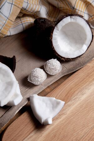 Coconut and sweet chocolate coconut truffles. Coconut shell, coconut flakes, small pieces of crashed nut and white chocolate coconut sweets on a wooden background. Tropical fruit coconut in the shell.