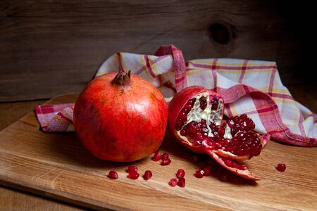 Composition of ripe red pomegranate and cracked pomegranate on a wooden background. Close up view of ruby seeds pomegranate fruit.