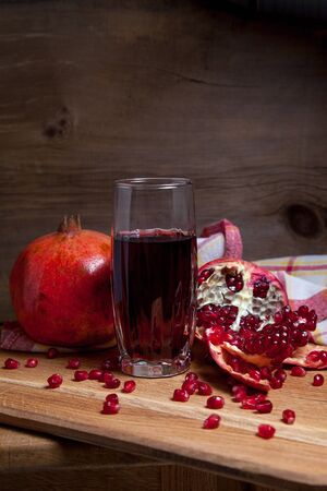 Composition of ripe red pomegranate and glass of fresh rudy juice on a wooden background. Close up view of ruby seeds pomegranate fruit and sweet fresh juice in glass. Stock Photo
