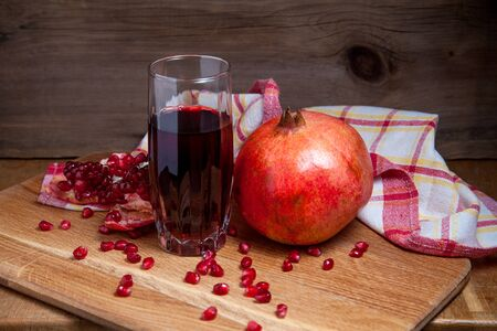 Composition of ripe red pomegranate and glass of fresh rudy juice on a wooden background. Close up view of ruby seeds pomegranate fruit and sweet fresh juice in glass.