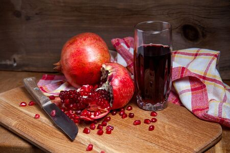 Composition of ripe red pomegranate with vintage knife and glass of fresh rudy juice on a wooden background. Close up view of ruby seeds pomegranate fruit and sweet fresh juice in glass.