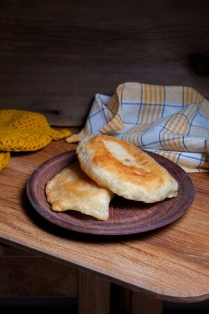 Clay plate with two of individual fried pies with meat on wooden table. Tatar traditional pies.