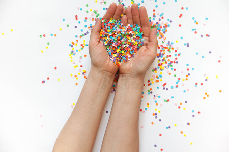 shredded: Hands holding festive confetti. White background. Small circles of colored paper. Heart made of colored confetti.