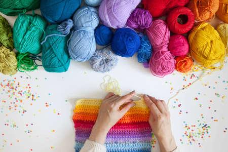paletas de caramelo: Bolas de hilo color. Vista desde arriba. Todos los colores del arco iris. Muestra de tejido de punto. Manos de las mujeres son tejidas. Tejer.