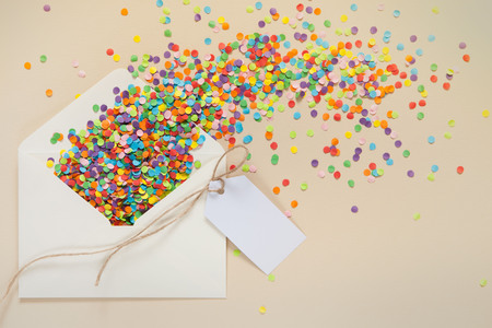 shredding: Colored confetti pours out of the envelope. Small circles of colored paper. White background. View from above.