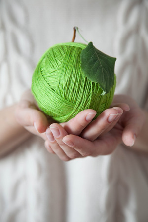 Ball of green wool in the form of an apple. Green apple of woolen thread. Hands holding a ball of wool. Light background. Knitted Sweater White. Stock fotó