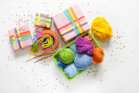 Balls of colored yarn. View from above. All the colors of the rainbow. Sample knit. Crochet. Gifts wrapped in colored paper. Holiday packages show. Imagens