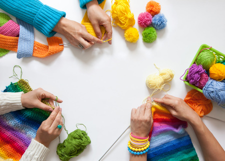 paletas de caramelo: Women crochet and knitting from colored yarn. View from above.