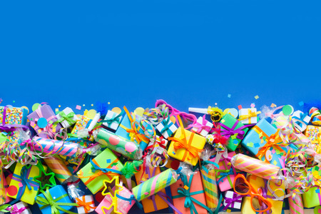 Many colored gifts lie and stand on a blue background.